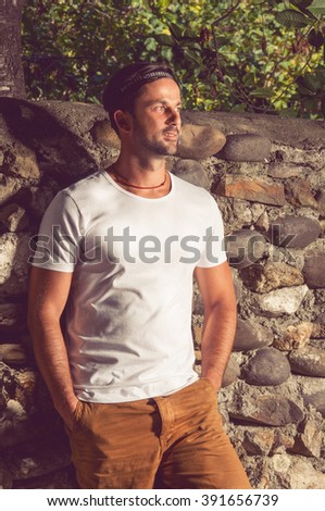 Portrait of handsome young hipster male standing outdoors and posing on a sunny day - stock photo