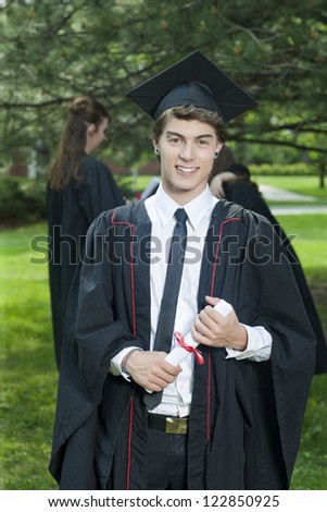 Portrait of handsome young male in graduation gown holding his diploma