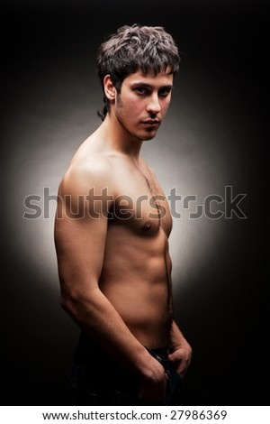 portrait of handsome young man against dark background - stock photo