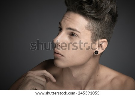 Portrait of handsome young man against dark grey background - stock photo