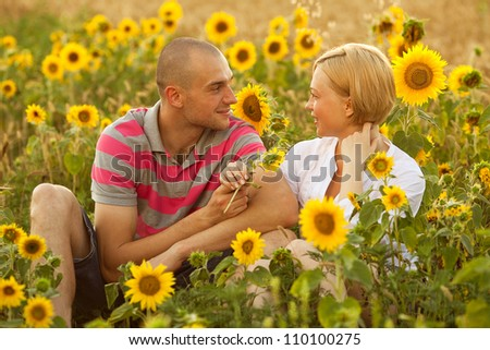 Portrait of handsome young man and beautiful woman sitting in the field of sunflowers and looking at each other. outdoor shot - stock photo