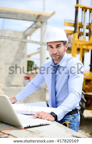 portrait of handsome young man architect on a building industry construction site - stock photo