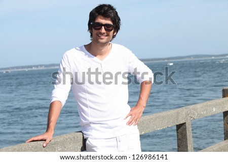 portrait of handsome young man at sea resort - stock photo