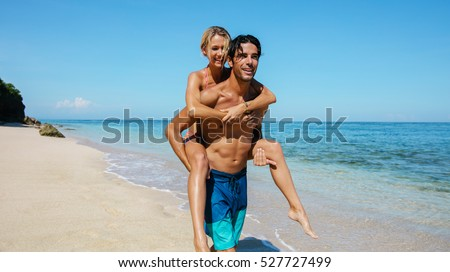 Portrait of handsome young man carrying girlfriend on his back and walking along the coast. Couple enjoying piggyback ride on the beach.