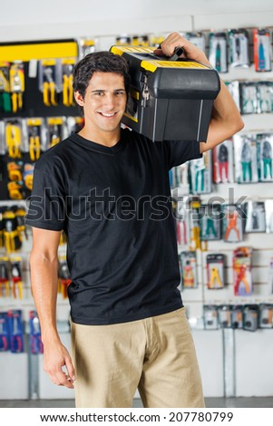 Portrait of handsome young man carrying toolbox on shoulder in hardware store