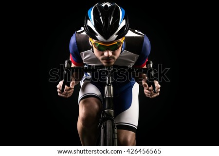 Portrait of handsome young man cycling indoor. Isolated on black. - stock photo