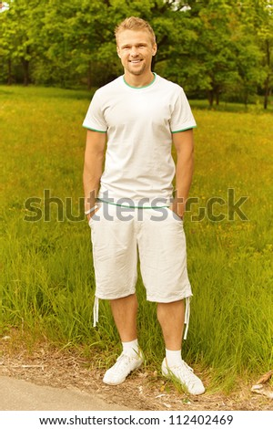 Portrait of handsome young man dressed in white, against green of summer park.