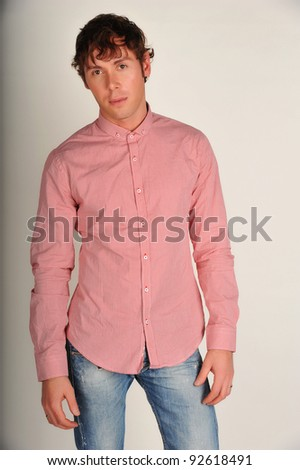 Portrait of handsome young man in casual clothes standing over white background with hands on hips