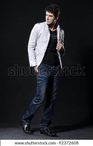 Portrait of handsome young man in casual standing over black background - stock photo