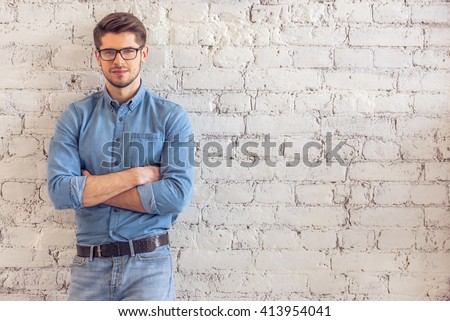 Portrait of handsome young man in jeans clothes and eyeglasses looking at camera and smiling, standing against white brick wall - stock photo