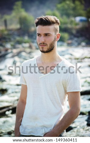 Portrait of handsome young man in white t-shirt outdoors, looking to a side - stock photo