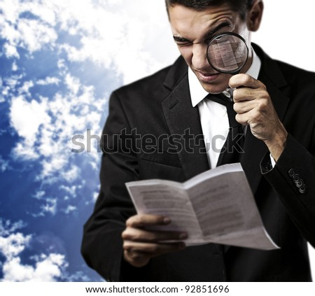 portrait of handsome young man looking a contract through a magnifying glass against a blue sky background - stock photo