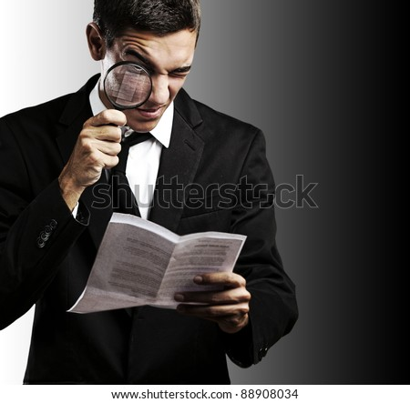 portrait of handsome young man looking a contract through against a black background - stock photo