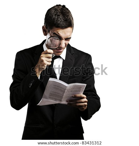 portrait of handsome young man looking a contract through against a white background - stock photo