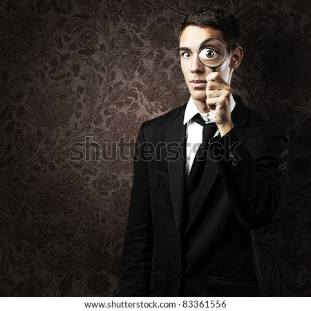 Portrait of handsome young man looking through a magnifying glass against a grunge wall - stock photo
