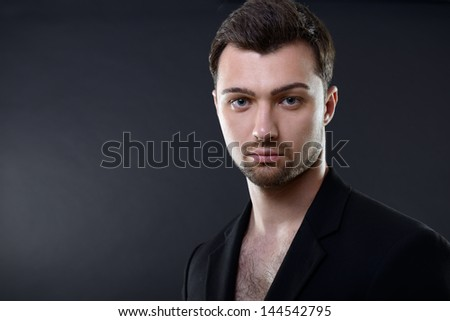 Portrait of handsome young man over black