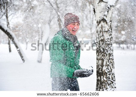 Portrait of handsome young man playing with snow outdoor in winter park on holidays