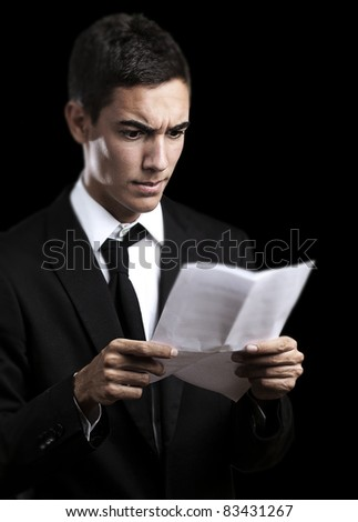 portrait of handsome young man reading a contract on black background
