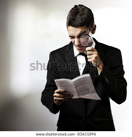 portrait of handsome young man reading a contract through a magnifying glass