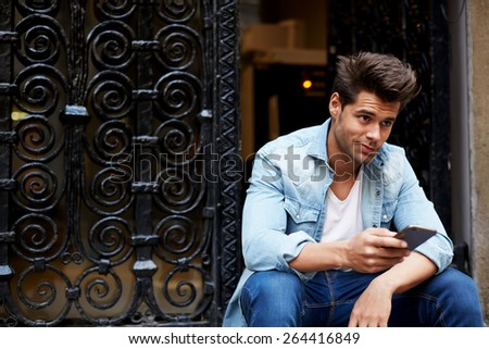 Portrait of handsome young man sending a text message while sitting outside, young student sitting on the stairs typing, cropped shot of a fashionable man using his mobile phone in urban setting - stock photo