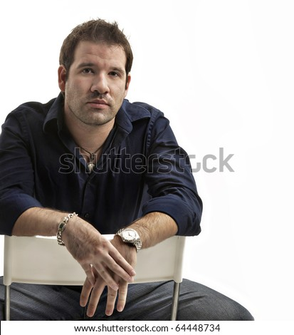 Portrait of handsome young man sitting on a chair isolated against white background