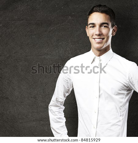 portrait of handsome young man smiling against grunge background - stock photo