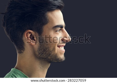Portrait of handsome young man smiling, isolated on gray background - stock photo