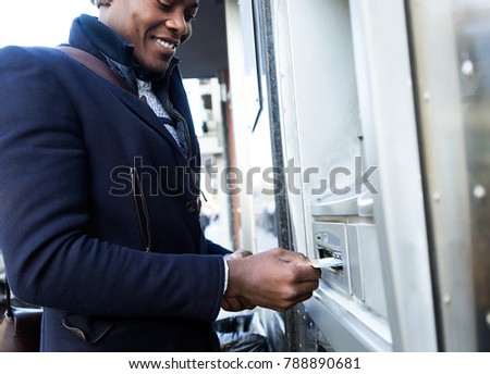 Portrait of handsome young man taking cash from ATM with credit card.