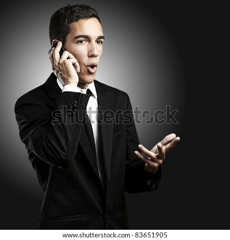 portrait of handsome young man talking on mobile against a black background - stock photo