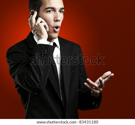portrait of handsome young man talking on mobile against a red background - stock photo