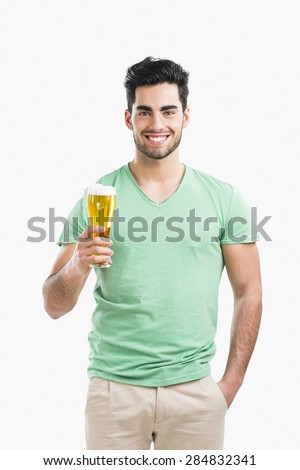 Portrait of handsome young man tasting a draft beer, isolated on gray background - stock photo