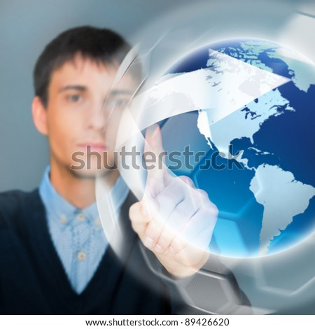 Portrait of handsome young man touching virtual globe. Global networking concept - stock photo