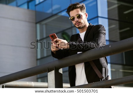 Portrait of handsome young man using his mobile phone in the street.