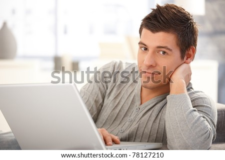 Portrait of handsome young man using laptop computer, looking at camera, smiling.?