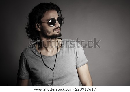Portrait of handsome young man with beard and mustache against light grey background - stock photo
