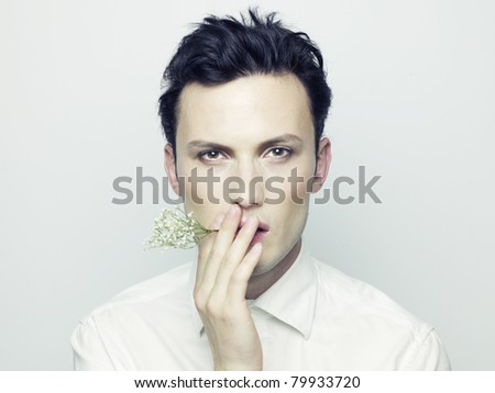 Portrait of handsome young man with flower in his mouth - stock photo