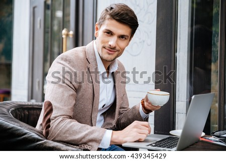 Portrait of handsome young man with laptop sitting and drinking coffee in outdoor cafe