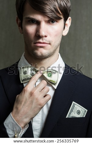 Portrait of handsome young man with money in pocket of jacket. Bow-tie in the form of bills. - stock photo