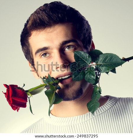 Portrait of handsome young man with rose - stock photo