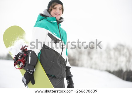 Portrait of handsome young man with snowboard in snow - stock photo