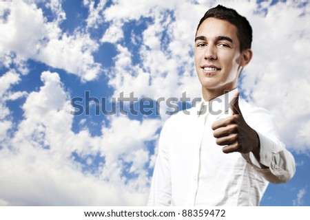 portrait of handsome young man with thumb up against a blue sky background - stock photo