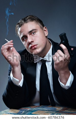 Portrait of handsome young mobster with cigarette and gun - stock photo