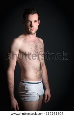 Portrait of handsome young muscular man in white underpants in front of dark background