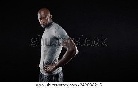 Portrait of handsome young muscular man posing against black background. African male fitness model looking at camera with his hands on hips with copyspace. - stock photo