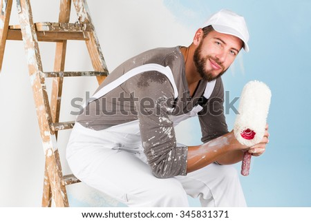 Portrait of handsome young smiling painter in white dungarees, splattered shirt and cap, leaning on a vintage ladder with paint roller