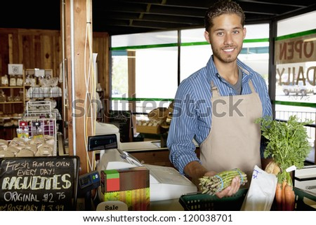 Portrait of handsome young store clerk holding vegetable in supermarket - stock photo
