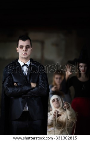 Portrait of handsome young Vampire with other Halloween characters in the background - stock photo