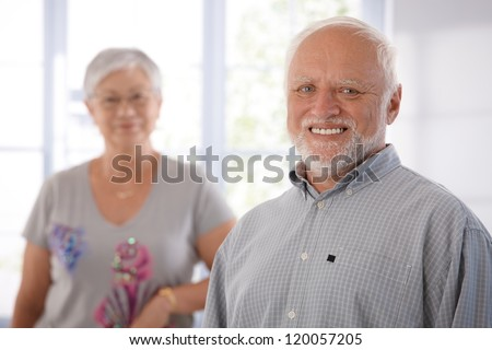 Portrait of happily smiling old man, woman in the background. - stock photo