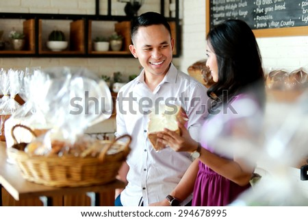 portrait of happiness of young couple shopping at bakery shop - stock photo