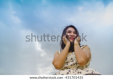 portrait of happiness woman stays outdoor with sky background - stock photo